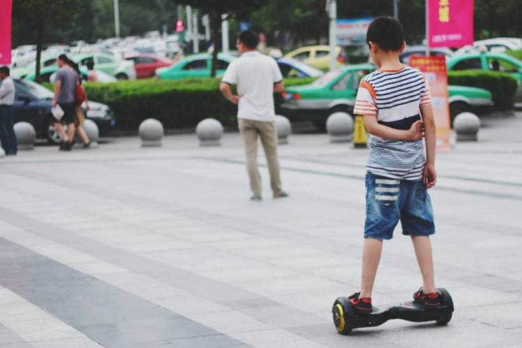 Boy In Segway On Street