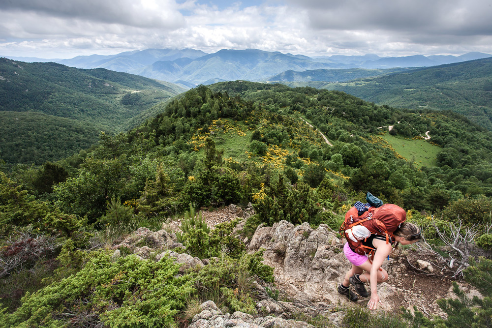 A woman climbs up a steep rocky path on a mountain hiking trip